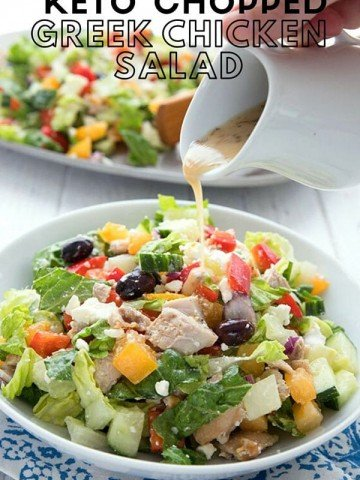 Titled image of chopped Greek chicken salad in a white bowl, over a blue napkin, with dressing being poured out of a small white pitcher.