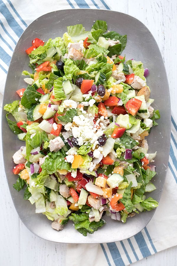 Top down photo of Greek Chopped Salad on a pewter platter, over a blue and white striped napkin