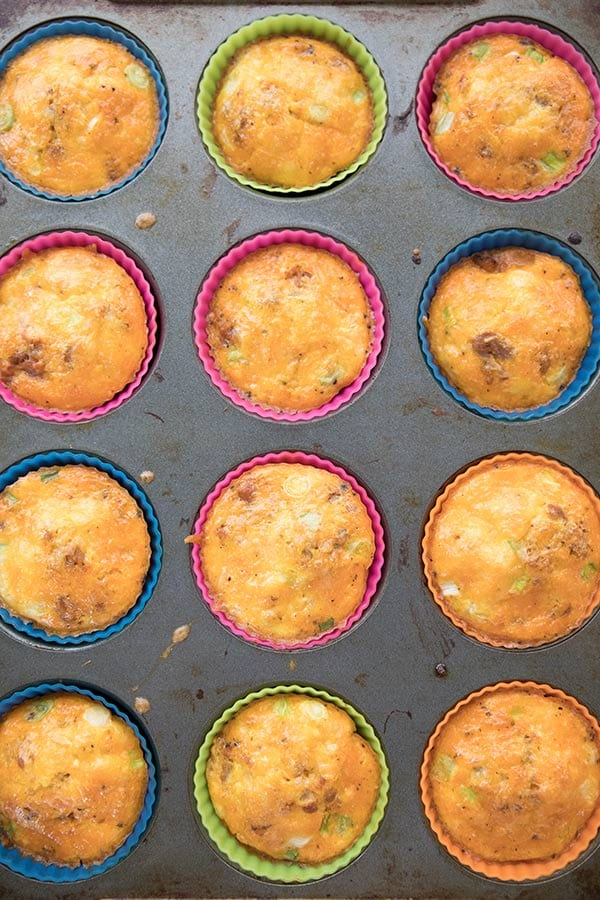 Top down photo of keto egg muffins still in their silicone liners in a metal muffin pan