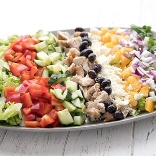 A pewter platter layered with the ingredients for chopped Greek chicken salad