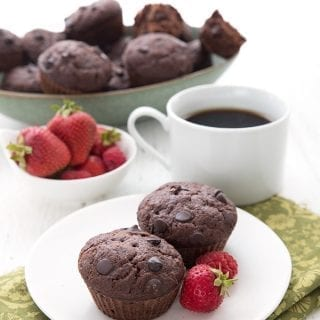 Two double chocolate zucchini muffins sit on a white plate over a green patterned napkin. A cup of coffee, a bowl of berries, and a bowl of muffins in the background.