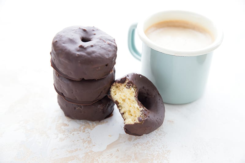 A cup of coffee with a stack of mini keto donuts.