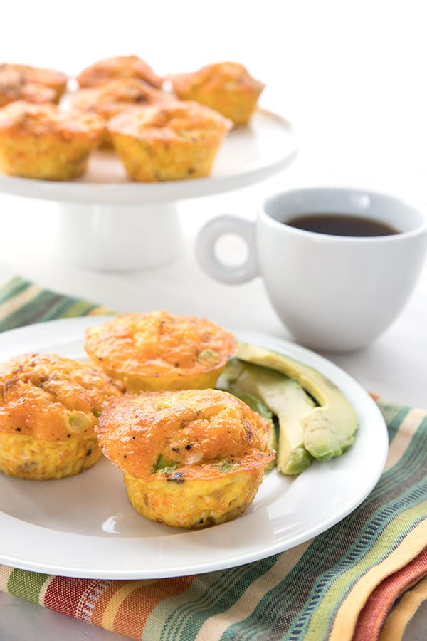 A white plate with three keto egg muffins sits over a striped napkin. A cup of coffee and a cake platter with more egg muffins in the background.