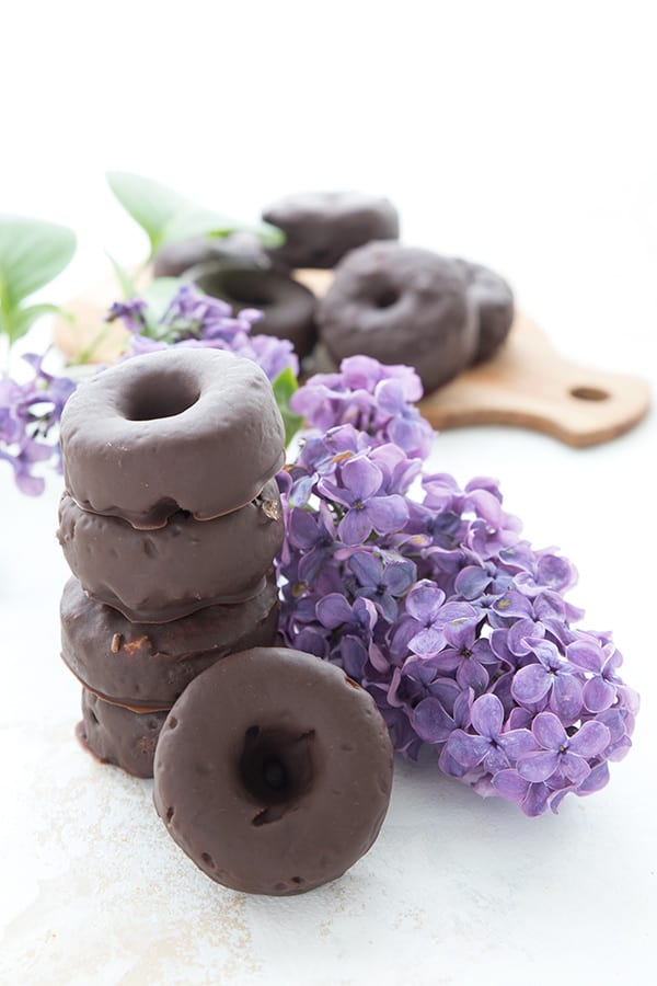 A stack of keto mini donuts with a sprig of lilacs. A cutting board in the background with more donuts on it.