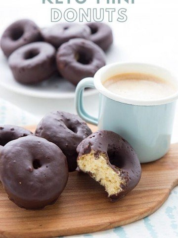 Titled image: a small cutting board with a cup of coffee and some chocolate covered mini donuts. A bite is taken out of the front donut. There is a white plate in the background with more donuts.