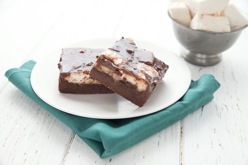 Two Mississippi Mud Bars on a white plate over a teal napkin, with a bowl of marshmallows in the background.