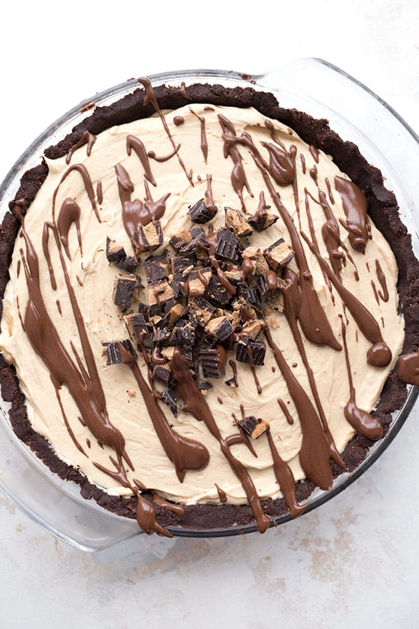 Top down photo of keto vegan peanut butter pie on a white table. The pie is in a glass pie plate with a drizzle of chocolate and keto peanut butter cups chopped up on top.