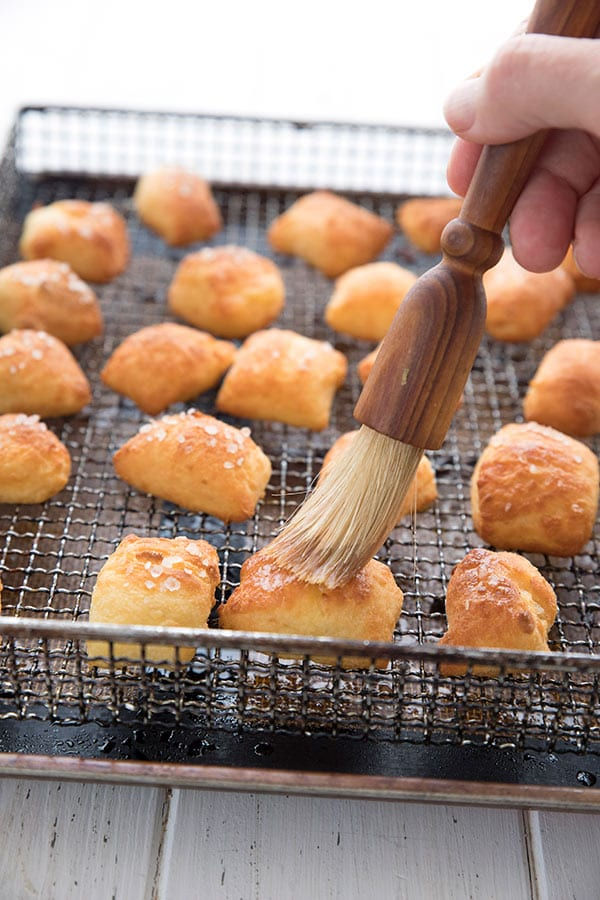 Brushing butter over air fryer pretzel bites on the air fryer rack.