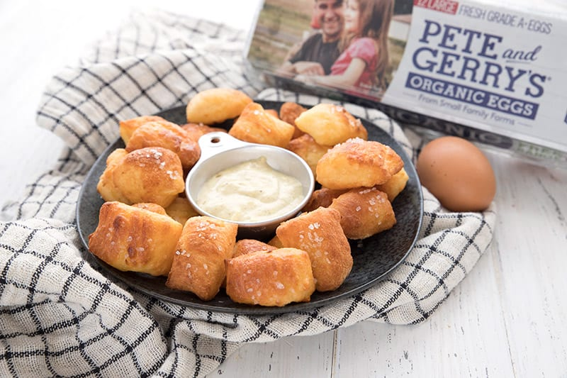 Keto pretzel bites on a black plate with mustard dipping sauce. A carton of organic eggs in the background.