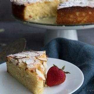 Titled image of keto almond ricotta cake. A slice of cake on a white plate with a strawberry, the rest of the cake on a stand in the background.