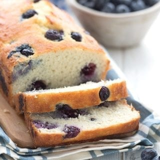 Close up shot of keto blueberry bread, sliced on a cutting board, with blueberries all around.