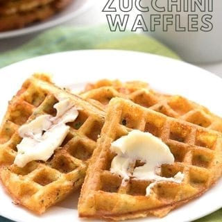 Titled image of keto zucchini waffles on a plate, slathered with butter, over a green napkin. A cup of coffee in the background.