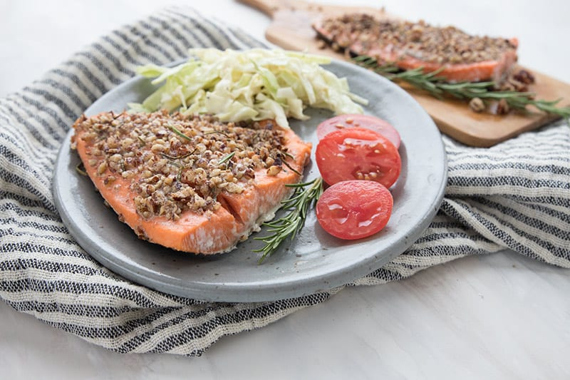 A grey plate with pecan crusted salmon, coleslaw, and fresh sliced tomatoes sits on a grey and white striped napkin. A cutting board with another piece of salmon in the background.