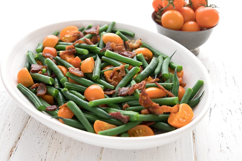 A white oval dish on a white table, filled with green beans, tomatoes, and bacon.