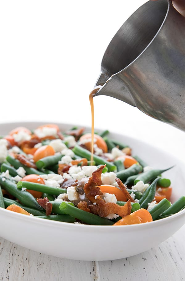 Dijon vinaigrette being poured from a pewter pitcher onto fresh green bean salad with bacon.