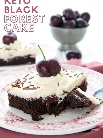 Titled image of a piece of keto Black Forest Cake on a red patterned plate, with a bowl of cherries in the background