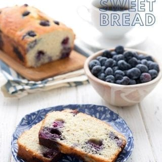 Titled image of keto blueberry coconut flour bread. Two slices on a blue patterned plate, in front of a bowl of blueberries, with the rest of the loaf in the background.