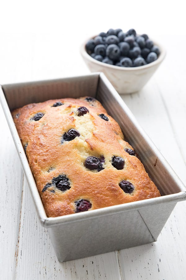 Keto blueberry bread in the pan, with a bowl of blueberries in the background