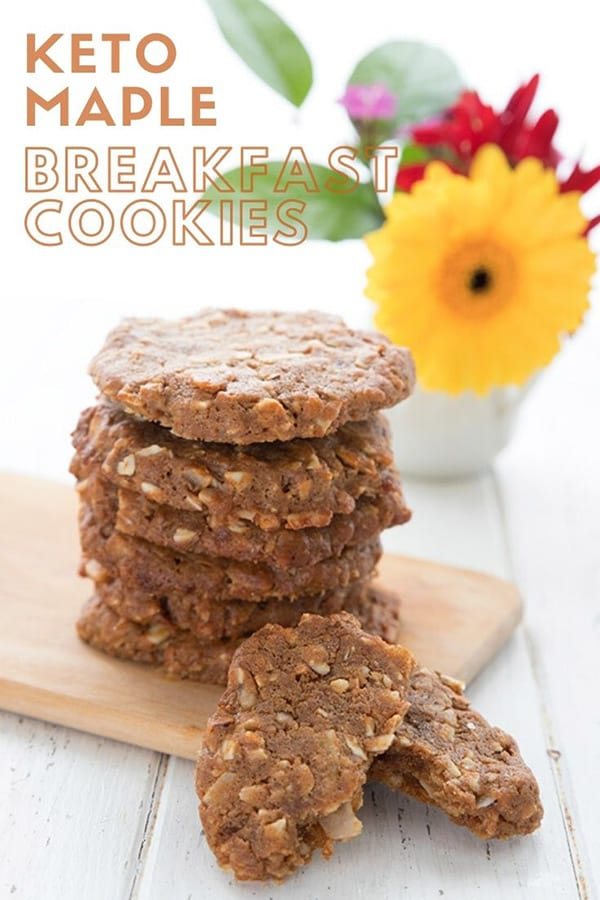 Titled image of keto breakfast cookies. The cookies sit on a wooden cutting board in a stack, in front of a vase of flowers.