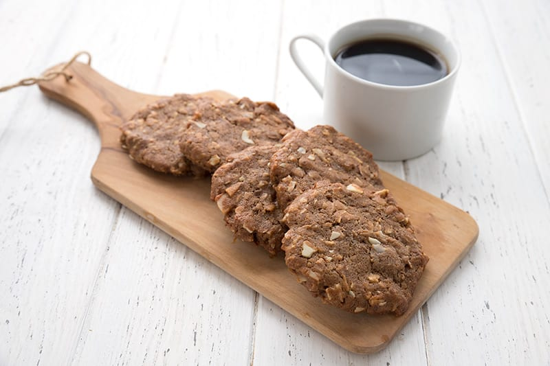 "Keto maple ""oatmeal"" breakfast cookies on a wooden cutting board on a white wooden table, with a cup of coffee in behind."
