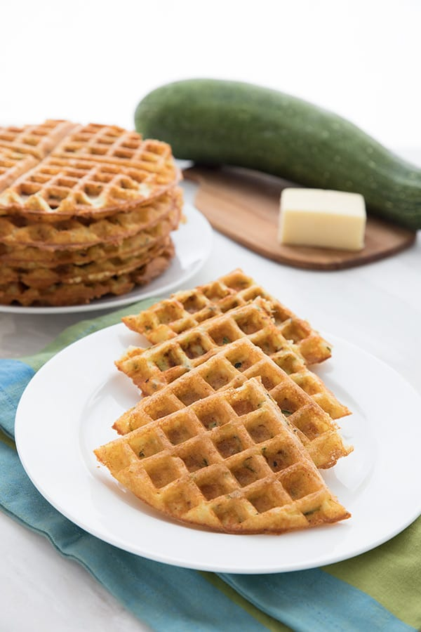 A white plate filled with keto cheddar zucchini waffles. More waffles and a zucchini and some cheese on a cutting board in the background