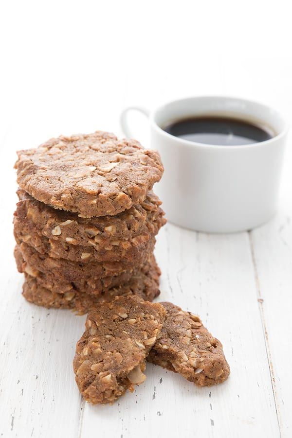 A stack of keto breakfast cookies with one broken open in front, on a white wooden table with a cup of coffee.