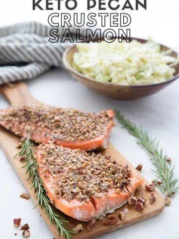 Titled Image: Keto Pecan Crusted Salmon with two pieces of salmon on a cutting board and a bowl of coleslaw in the background.