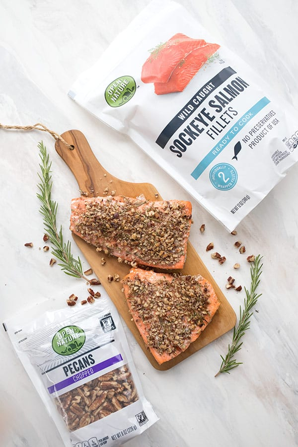 Top down photo of pecan crusted salmon on a wooden cutting board, with the package of salmon and pecans off to the sides.