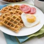 A white plate filled with eggs, zucchini waffles and tomatoes sites over a blue and green napkin