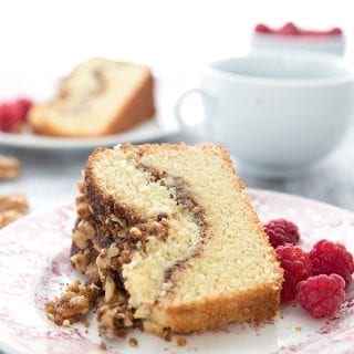 A slice of cinnamon walnut coffee cake on a red patterned plate, close up.