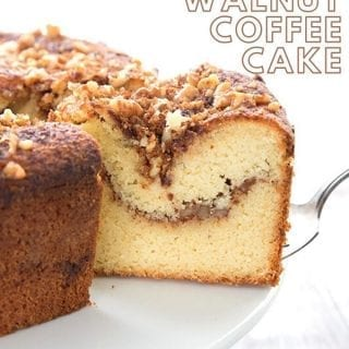 Titled image of Keto Cinnamon Walnut Coffee Cake, a slice being taken out of the large cake on a white cake stand.