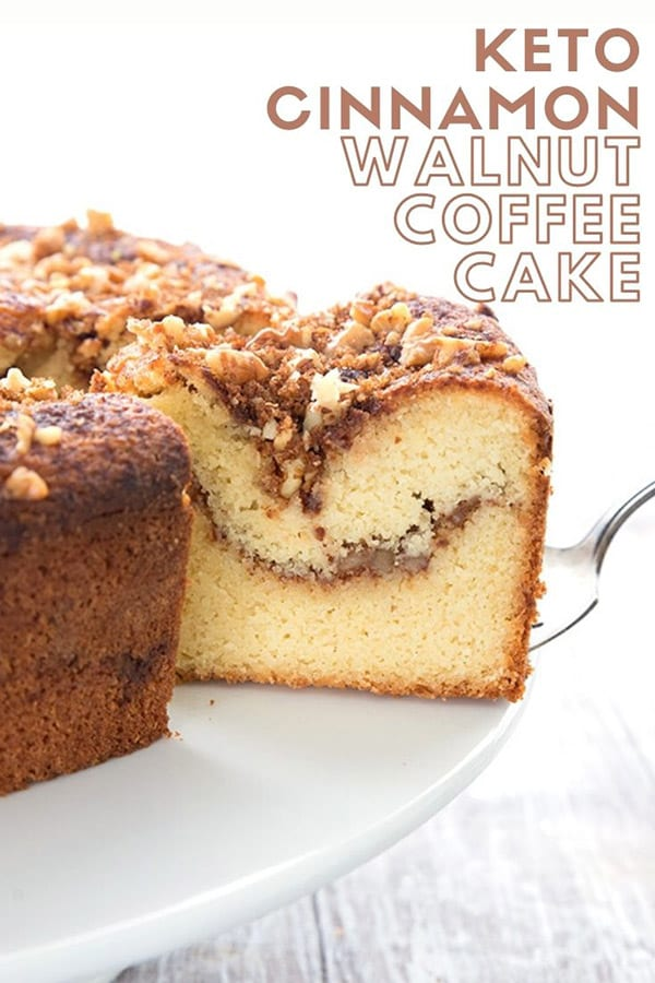 Keto Diet Explained  Titled image of Keto Cinnamon Walnut Coffee Cake, a slice being taken out of the large cake on a white cake stand.