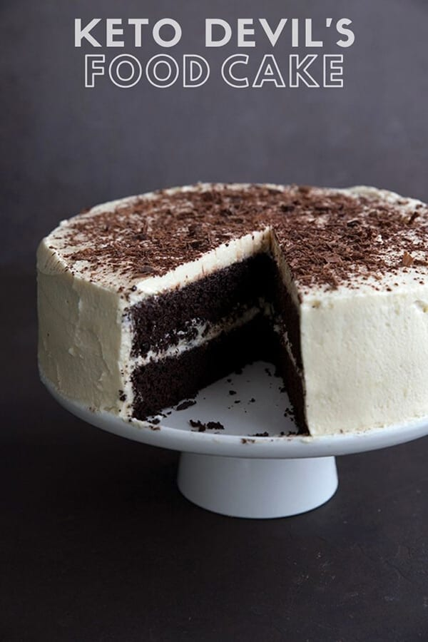 Titled image of keto devil's food cake on a white cake plate, with a slice cut out of it