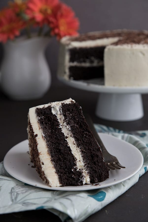 A slice of keto devil's food cake on a white plate in front of the rest of the cake.
