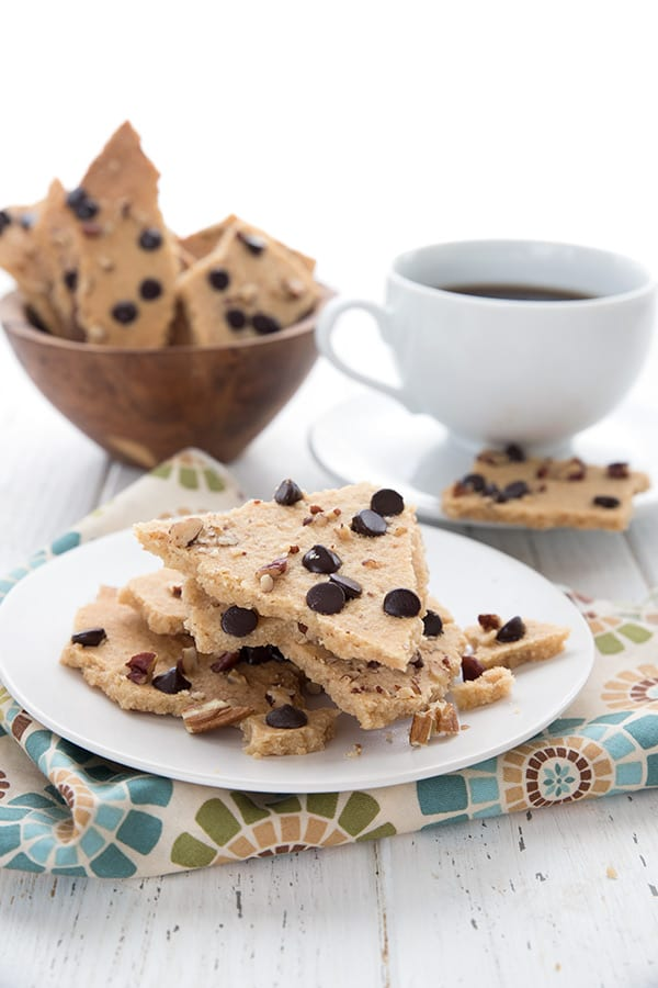 Pieces of chocolate chip cookie brittle sit on a white plate over a patterned napkin, with a cup of coffee in the background.