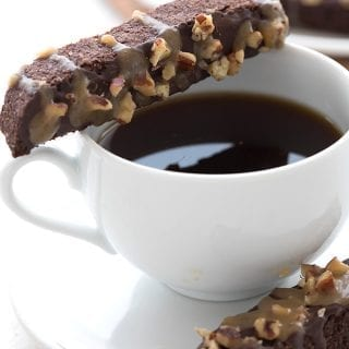 Close up shot of keto turtle biscotti balanced on a cup of coffee