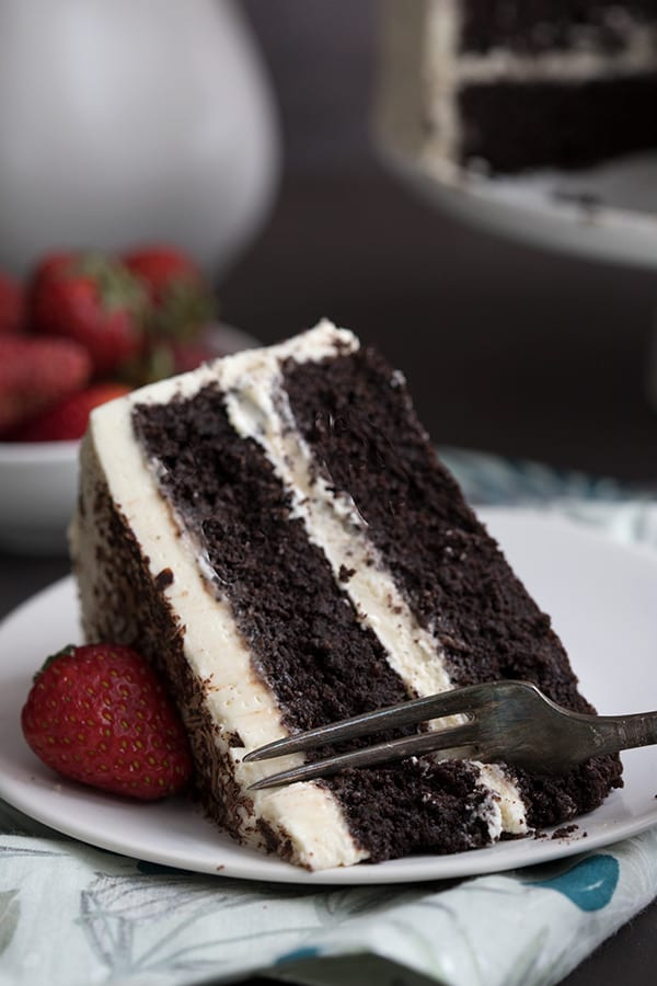 Close up shot of a fork digging into a piece of keto chocolate cake with vanilla frosting