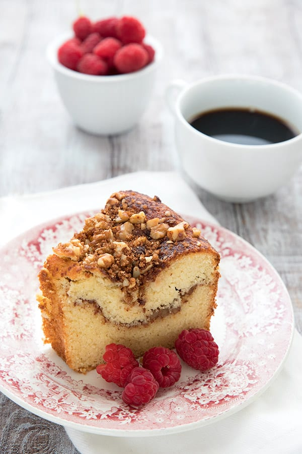 Keto Diet Explained  A slice of walnut coffee cake on a red patterned plate with raspberries.
