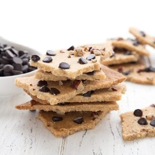 Keto cookie brittle piled around a white table with a bowl of chocolate chips.