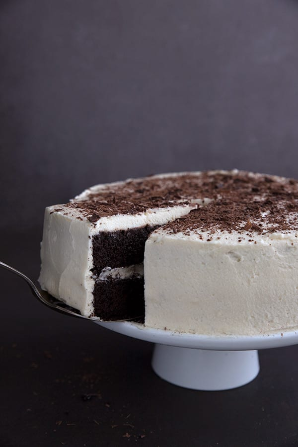 A spatula lifting a slice of keto devil's food cake away from the rest of the cake.