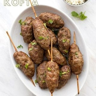 Titled image of Keto Lamb Kofta in a white oval dish with feta and cilantro