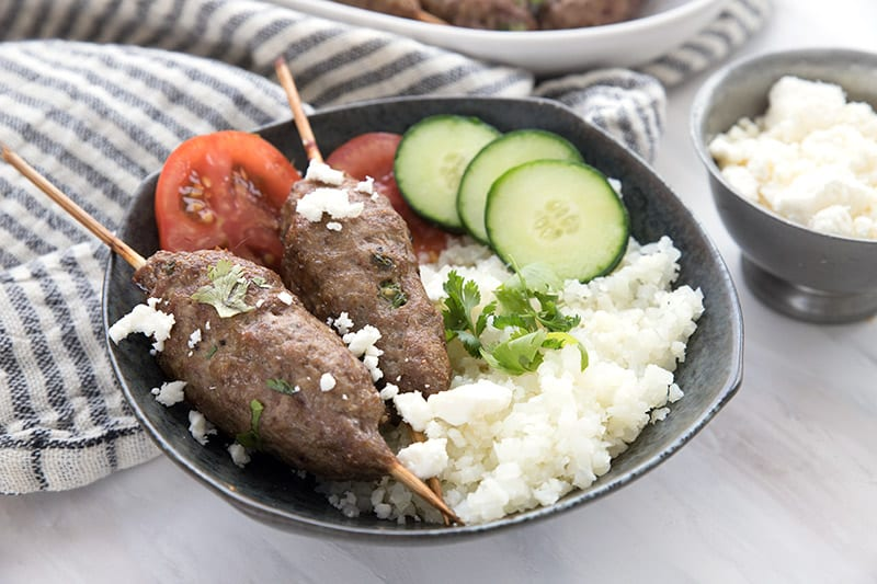 Lamb kofta in a black bowl with cauliflower rice, tomatoes, and cucumber