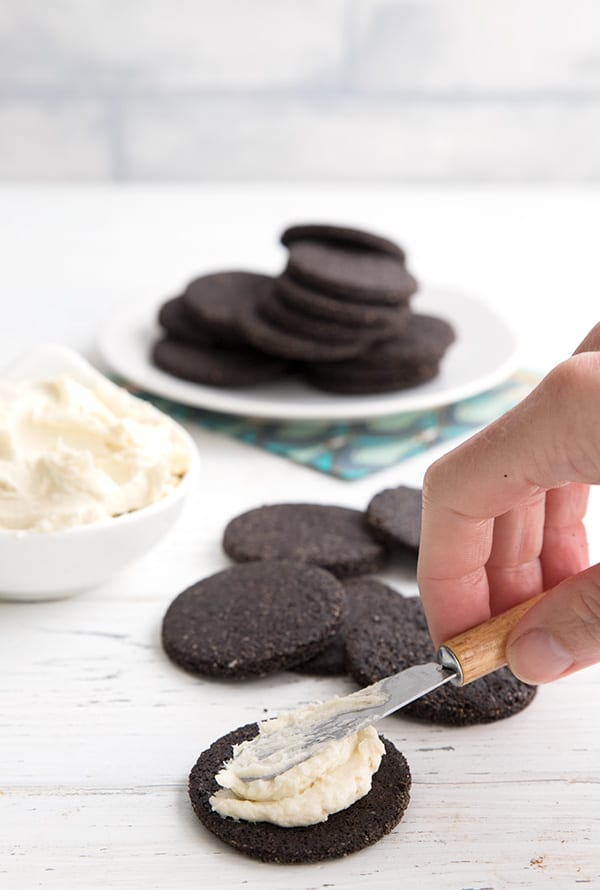 Spreading vanilla cream filling onto a chocolate wafer cookie for homemade keto oreos