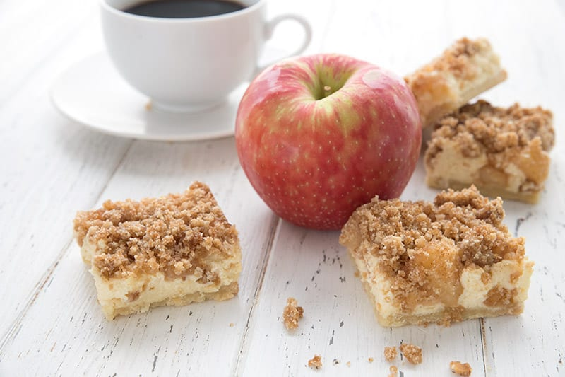 Keto Apple Pie Cheesecake Bars on a white wooden table with an apple and a cup of coffee