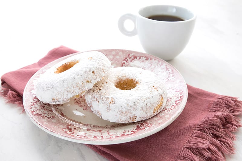 Keto powdered sugar donuts for two on a red patterned plate over a red napkin, with a cup of coffee in behind