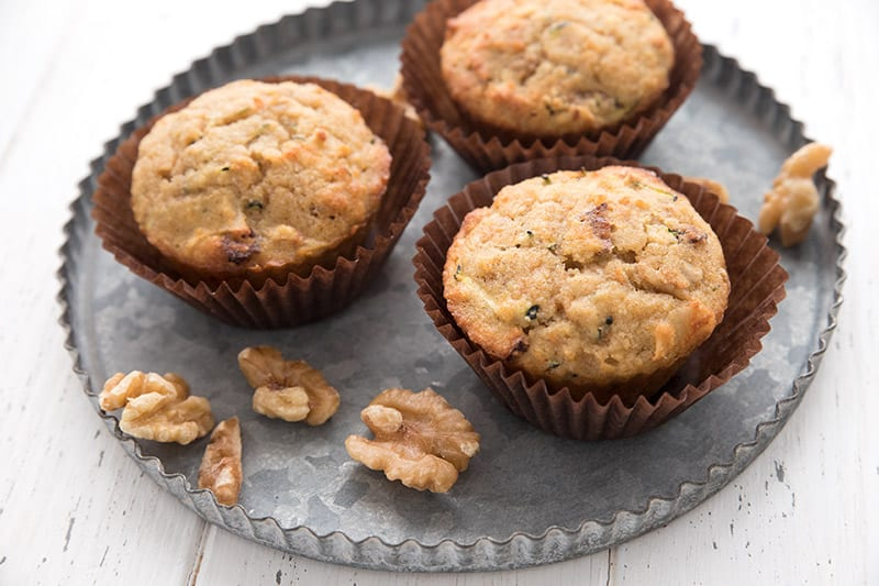 Three keto morning glory muffins on a metal plate with walnuts.