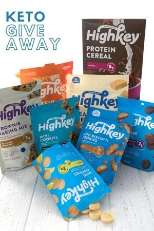 A collection of HighKey keto snacks, cookies, and cereals on a white wooden table.