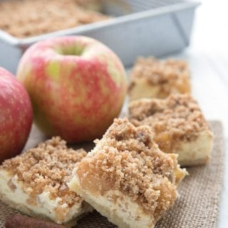 Keto apple pie bars on a burlap napkin over a white table.