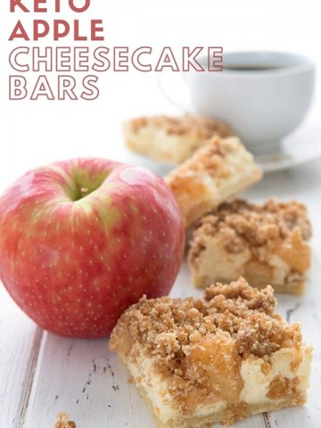 Titled image of keto apple cheesecake bars on a white table with an apple and a cup of coffee