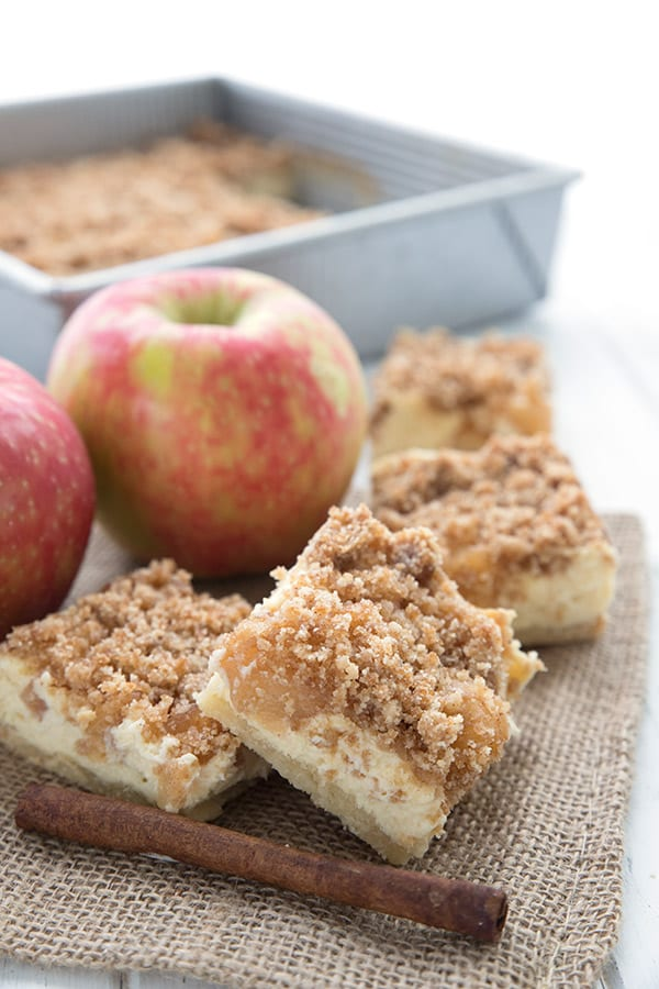 Keto apple pie bars on a burlap napkin over a white table.